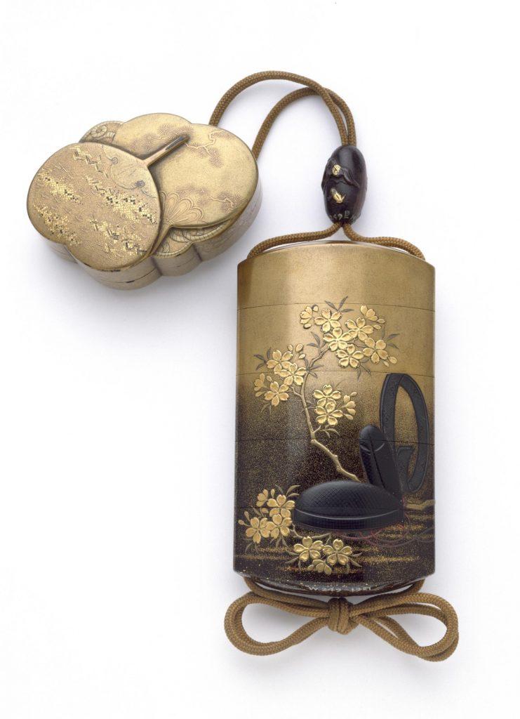 Siyah ve kırmızı renklerle çizilmiş Japonya saray adamı şapkası ve altın renkli kiraz ağacı çiçeği motifli onri kutusu, bele sarılan kumaşa asılan bu kutunun düşmemesini sağlayan ağırlık iseüst üste konmuş küçük iki yelpaze şeklinde yapılmış.