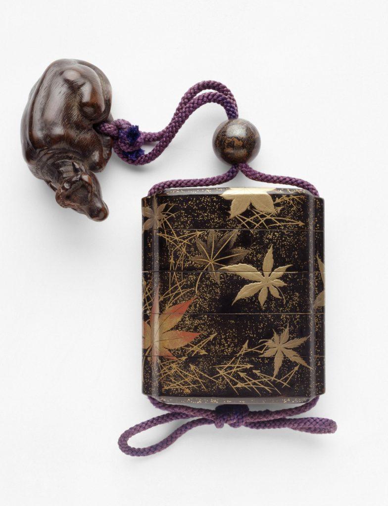 Samurayların cep niteliğinde kullandığı inro isimli kutu. Altın tozuyla süslenmiş siyah lake kutu, motifler ise akçaağaç yaprakları ve çam iğne yapraklarından oluşur.