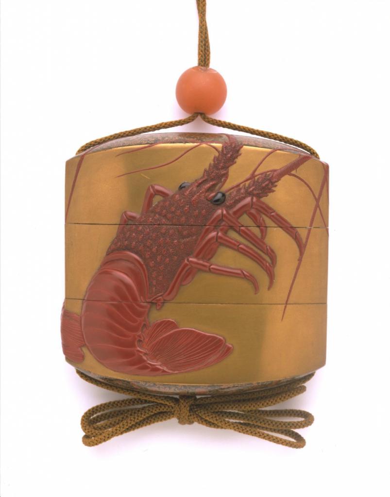 altın renkli lake kutunun üstüne kırmızı renkli karidese benzeyen kerevides motifi,