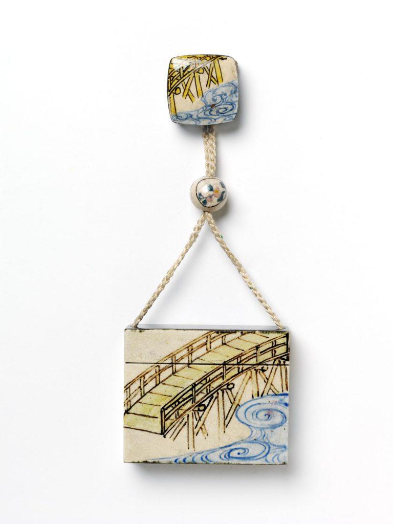 Mavi su dalgaları ve sarı köprülü inro adı verilen küçük eşya taşımaya yarayan minik kutu, kutunun ipindeki boncukta çiçek açmış ağaç dalı resmedilmiş.